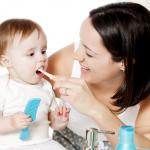 Ребенок чистит зубы под присмотром взрослых
